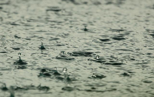 heavy rain drops in puddle