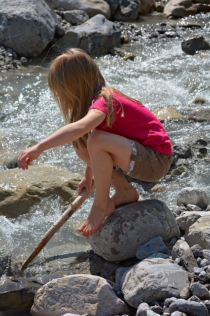 Girl Playing On Rocks